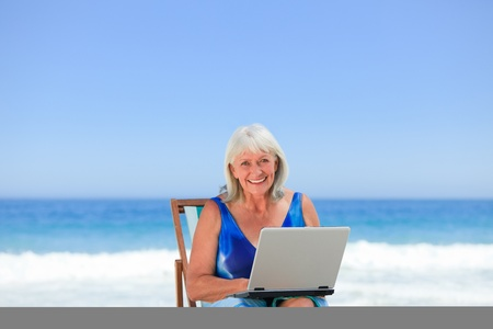 Woman working on her laptop on the beach photo
