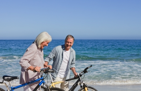 Retired couple with their bikes on the beach Stock Photo - 10174012