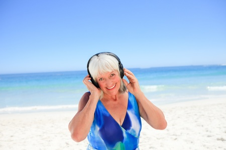 Senior woman listening to some music beside the sea photo