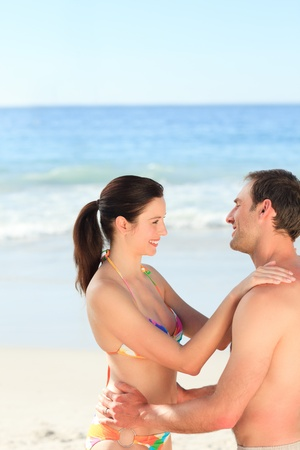 Adorable couple huging on the beach photo