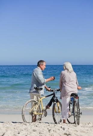 Senior couple with their bikes on the beach photo