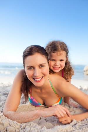 Mother and daughter lying down on the beach Stock Photo
