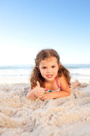 Little girl lying down on the beach photo
