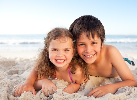 Little boy and his sister lying down on the beach photo