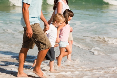 Family walking on the beach photo
