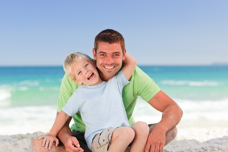 Attentive father with his son at the beach photo