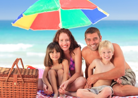 teen beach: Family picnicking under a sol umbrella on the beach Stock Photo