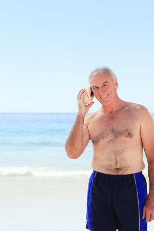 Senior man listening to his shell Stock Photo - 10169890