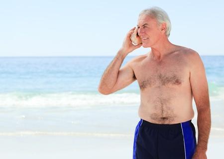 Senior man listening to his shell Stock Photo - 10163674