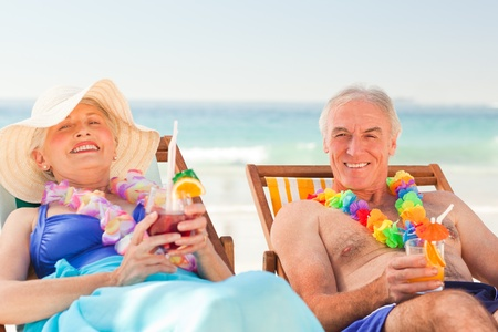 Couple drinking cocktails at the beach Stock Photo - 10173552