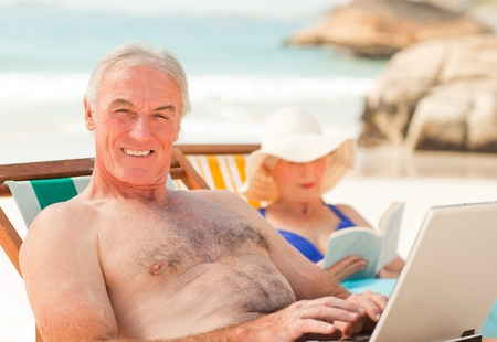 Man working on his laptop while his wife is reading at the beach  photo