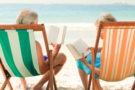 retired: Couple reading at the beach