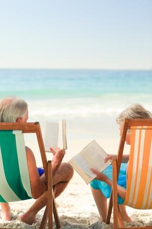 jubilados: Lectura Eldery pareja en la playa Foto de archivo