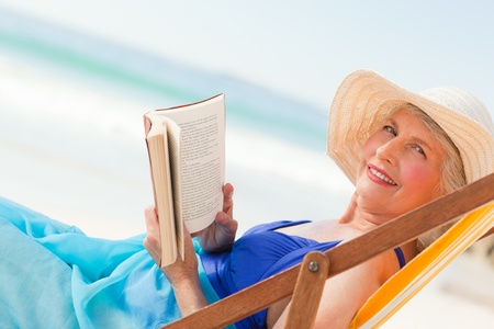 Elderly woman reading a book at the beach photo