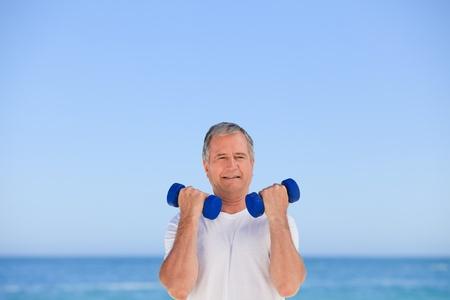 Mature man doing his exercises Stock Photo - 10164346