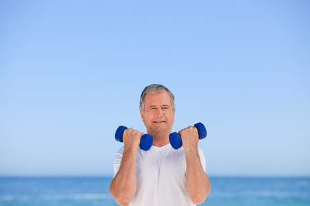Mature man doing his exercises Stock Photo - 10164346