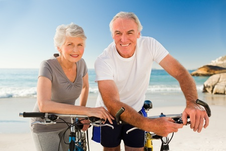 active seniors: Retired couple with their bikes on the beach