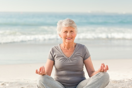 Senior woman practicing yoga on the beach photo
