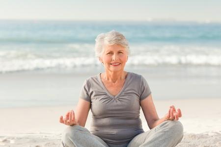 hand position: Superior de la mujer practicando yoga en la playa Foto de archivo