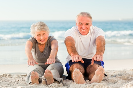 retired couple: Couple doing their streches at the beach