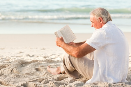 Man reading a book on the beach photo