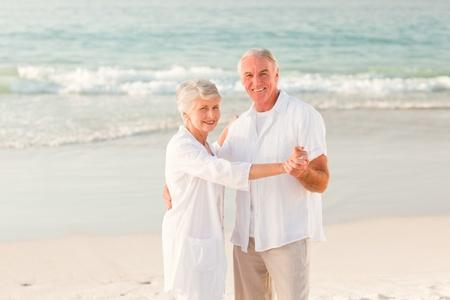 Elderly couple dancing on the beach Stock Photo - 10173514