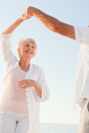 elderly couples: Senior couple dancing on the beach