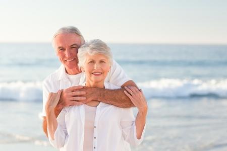 parejas caminando: El hombre abraza a su esposa en la playa