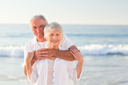 active couple: Man hugging his wife on the beach