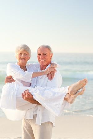 ancianos caminando: Hombre que lleva a su esposa en la playa Foto de archivo