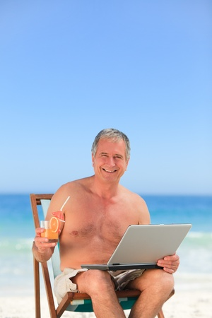 Retired man working on his laptop on the beach photo
