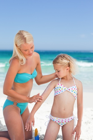 Mother applying sun cream on her daughter photo
