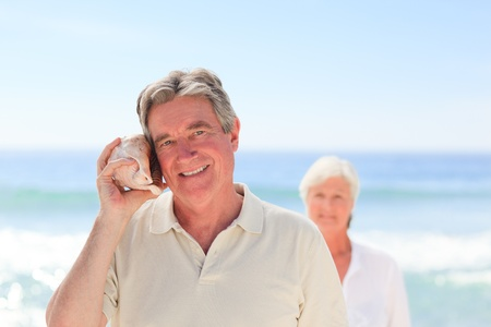 Man listening his shell with his wife behind him photo