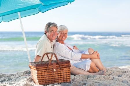 Elderly couple picniking on the beach photo