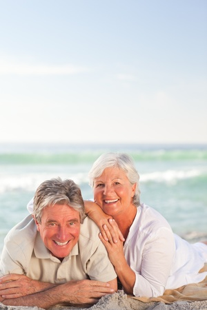 Elderly couple lying down on the beach photo