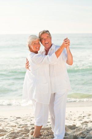 Elderly couple dancing on the beach Stock Photo - 10169894
