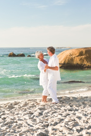 Retired couple dancing on the beach Stock Photo - 10173338