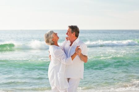 couple dancing: Baile pareja de jubilados en la playa