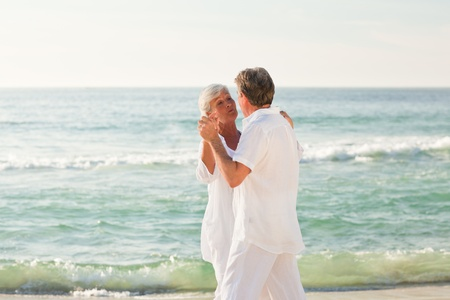 Retired couple dancing on the beach photo