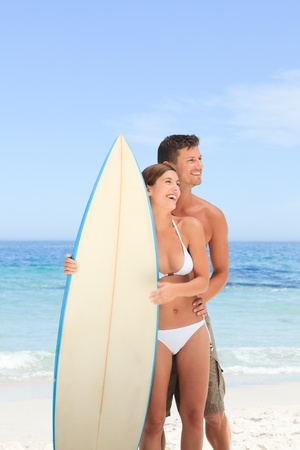 Couple with their surfboard photo
