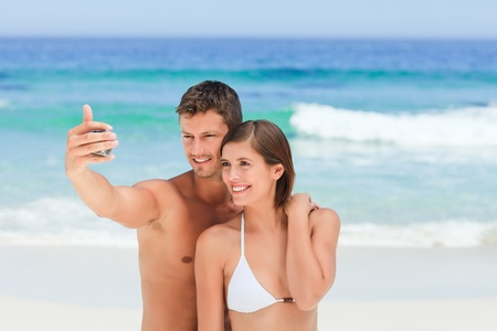 Lovers with their camera at the beach photo