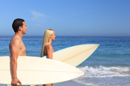 Lovers with their surfboards photo
