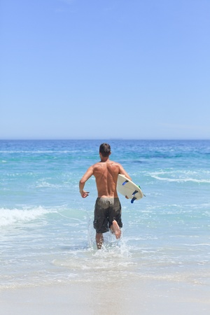Man running on the beach with his surfboard photo