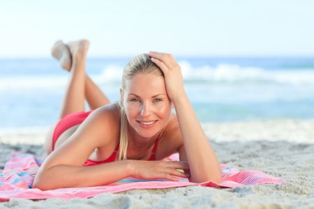 Beautiful woman lying down on the beach photo