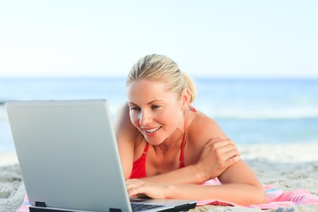 Lovely woman working on her laptop at the beach Stock Photo - 10183548