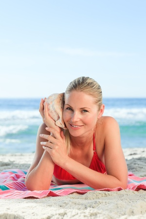 Woman listening to a shell Stock Photo - 10183793