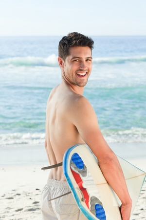 Handsome man beside the sea with his surfboard photo