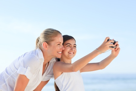 Little girl taking a photo of herself and her mother photo