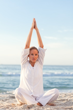 Active woman practicing yoga on the beach photo