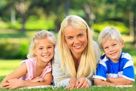 Mother with her children lying down in the park Stock Photo - 10184013